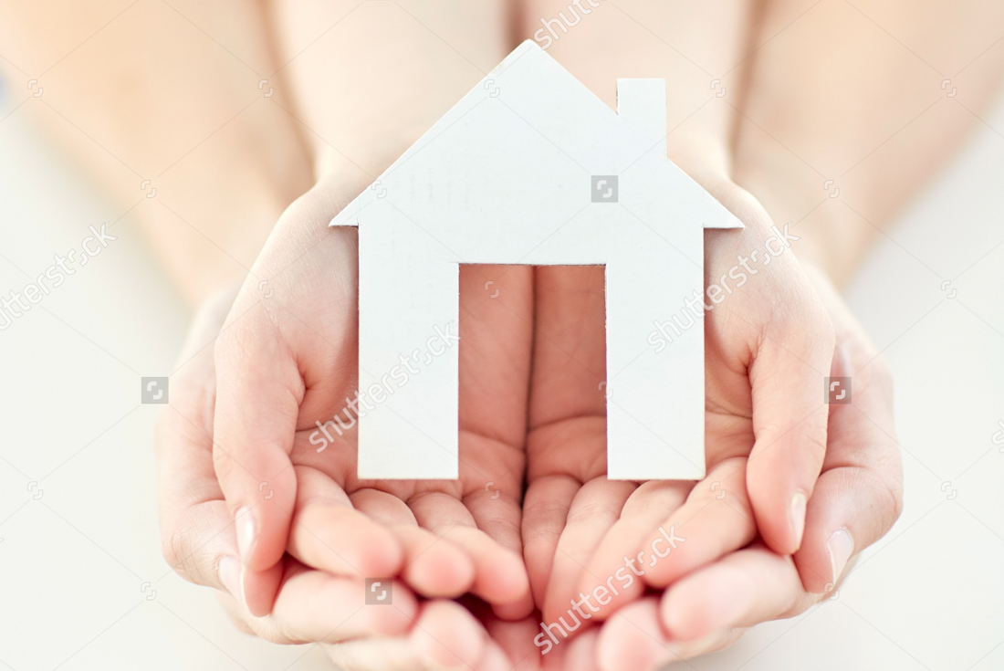 Zoomed in hands holding a paper cut out of a home.