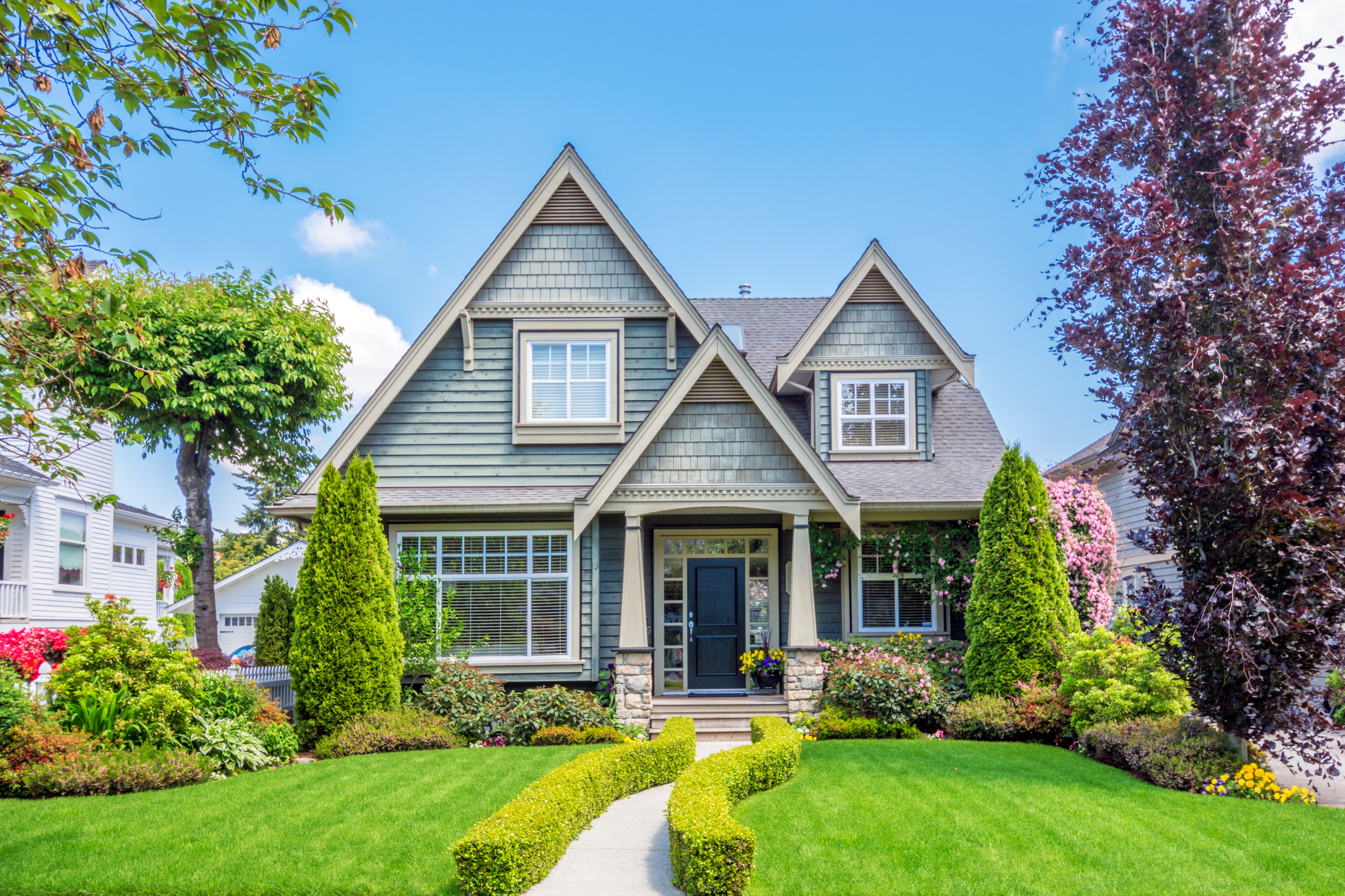 Beautiful Gray home with bright green grass on a sunny summer day.