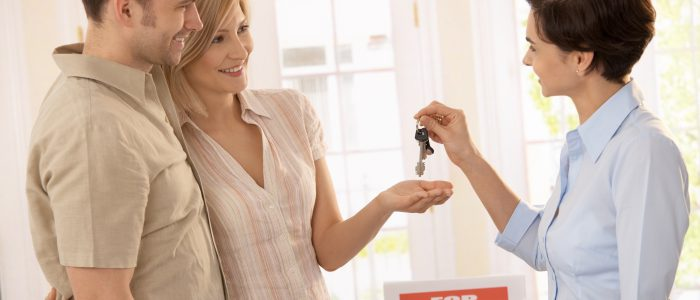 Estate agent handing over keys of new house to smiling couple.