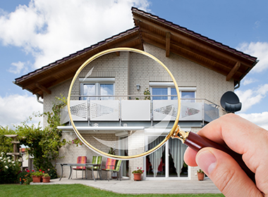 Magnifying Glass in focus looking at a home