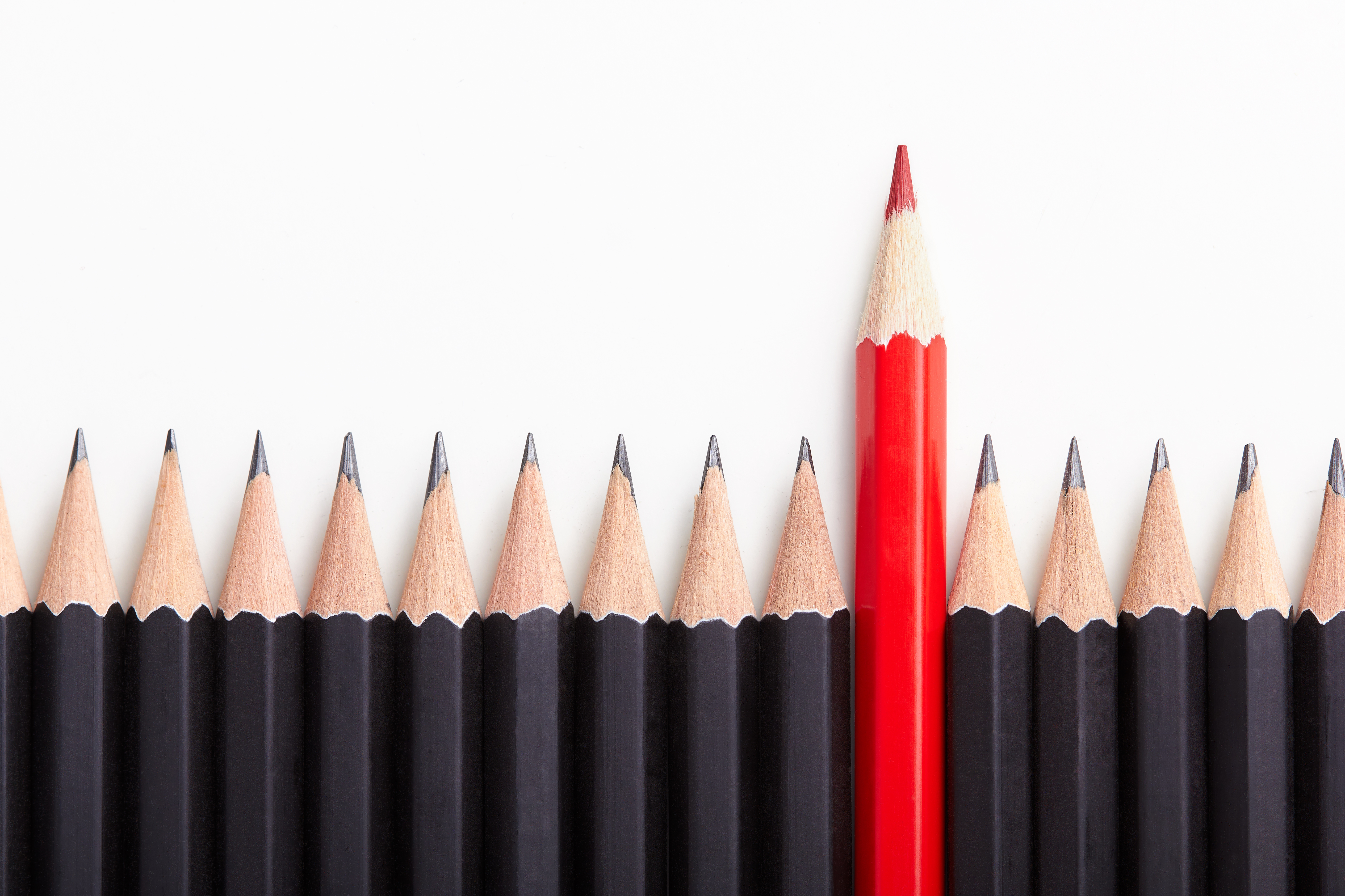 Red pencil standing out from crowd of plenty black pencils on a white table.