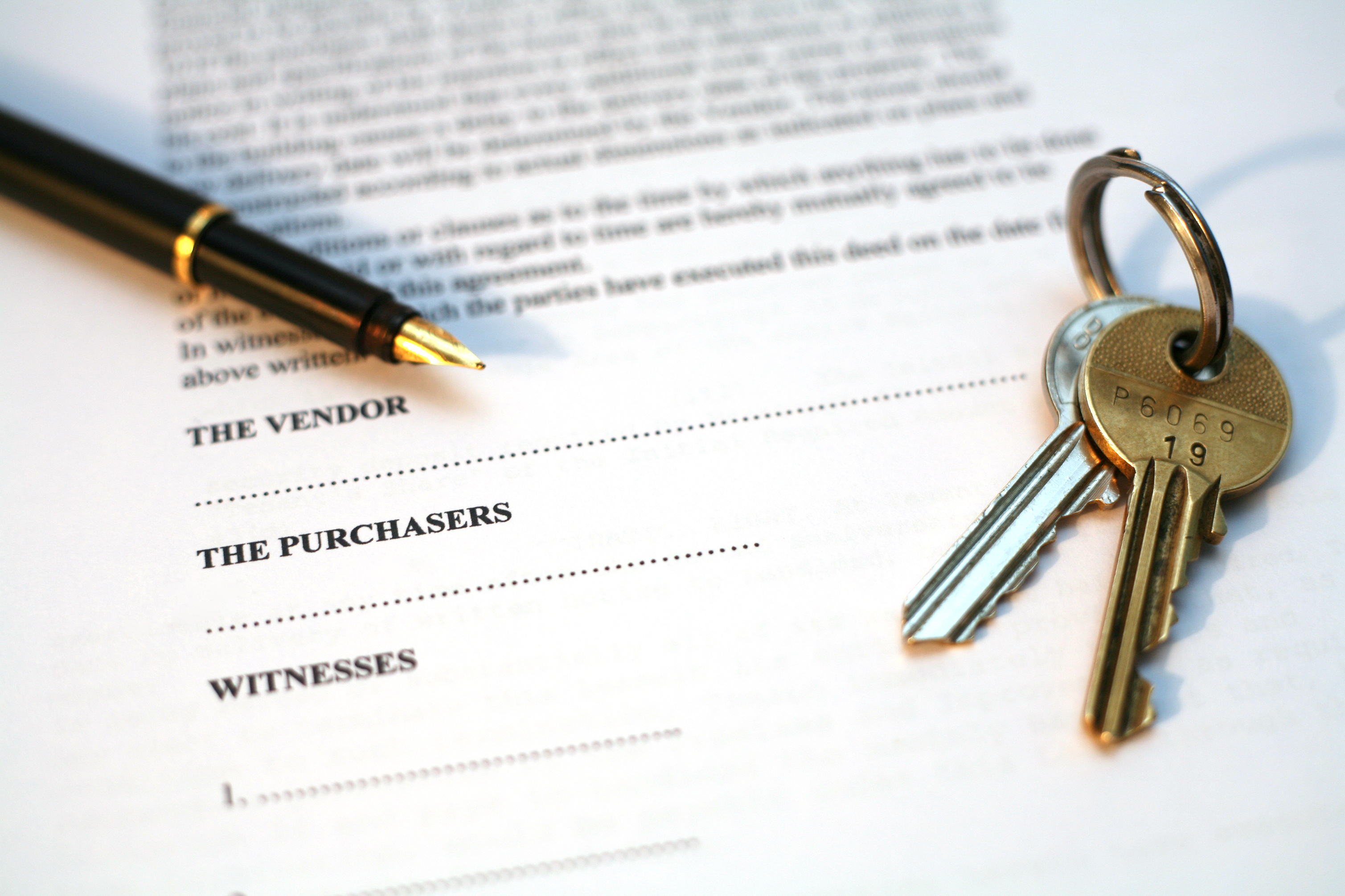 legal document for sale of real estate property in europe, with a gold-nibbed fountain pen and house keys