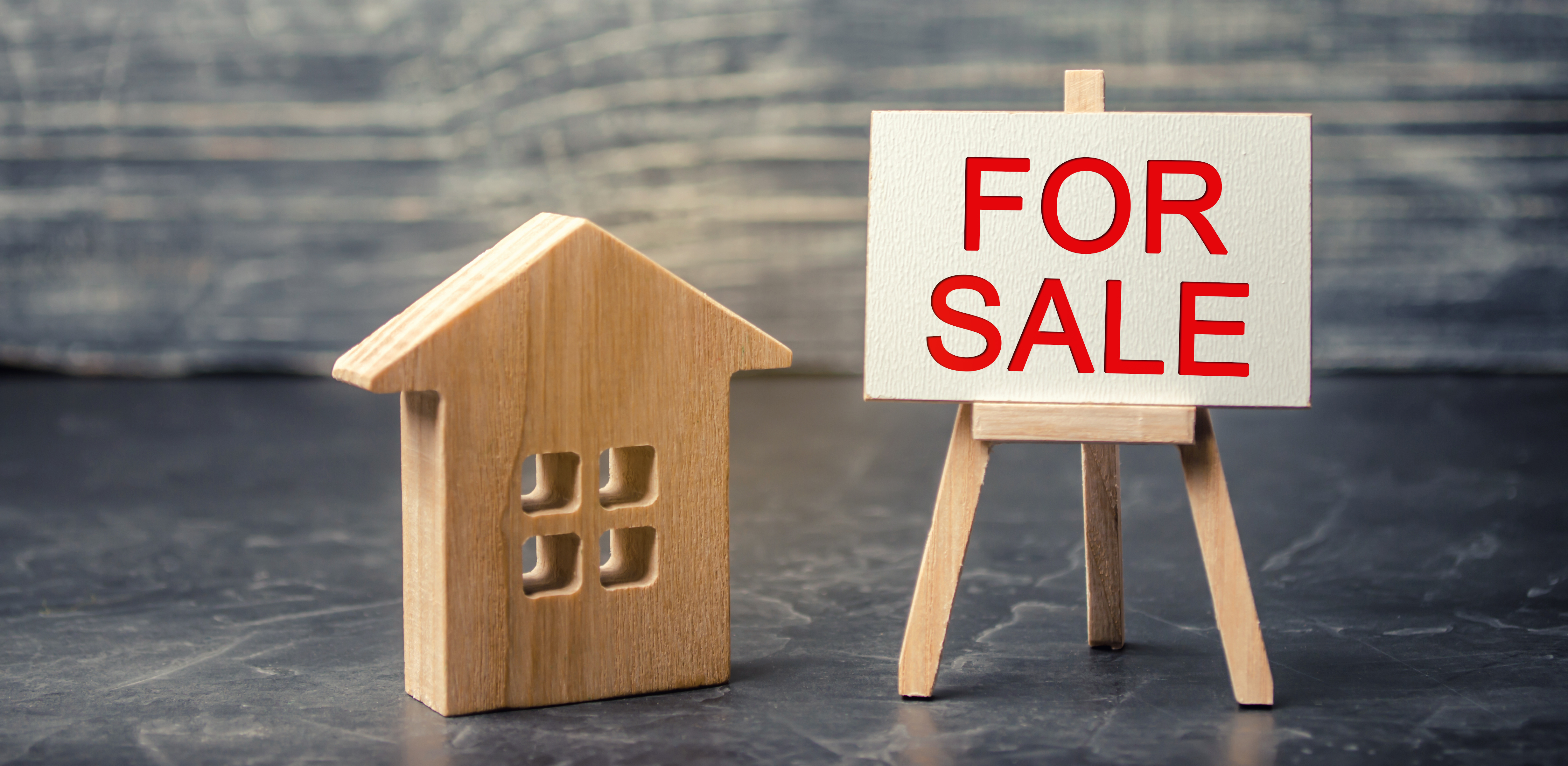 "wooden house and dollars with the inscription ""for sale"". sale of property, home. affordable housing. sale of apartments. real estate agent services. realtor"