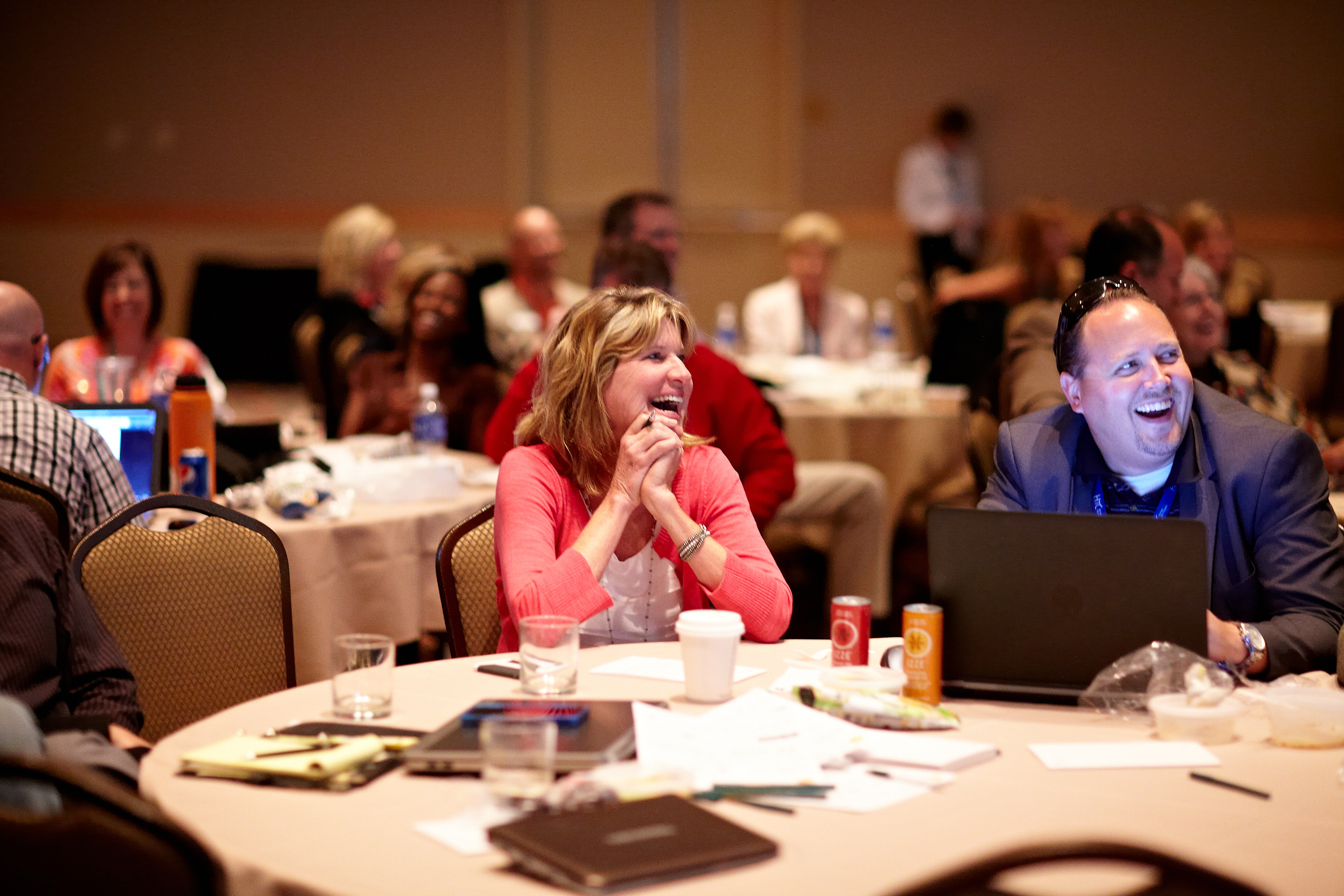 Image of two event attendees smiling during a Keynote speaker presentation