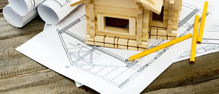 Building house. House construction. Many drawings for building and small wooden house on old wooden background.