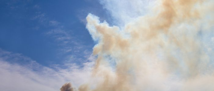 Smoke billowing in the air from a wildfire in Colorado with the sun shining through the smoke.