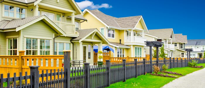 Housing lined up with a short fence lining the bright green grass on a summer day