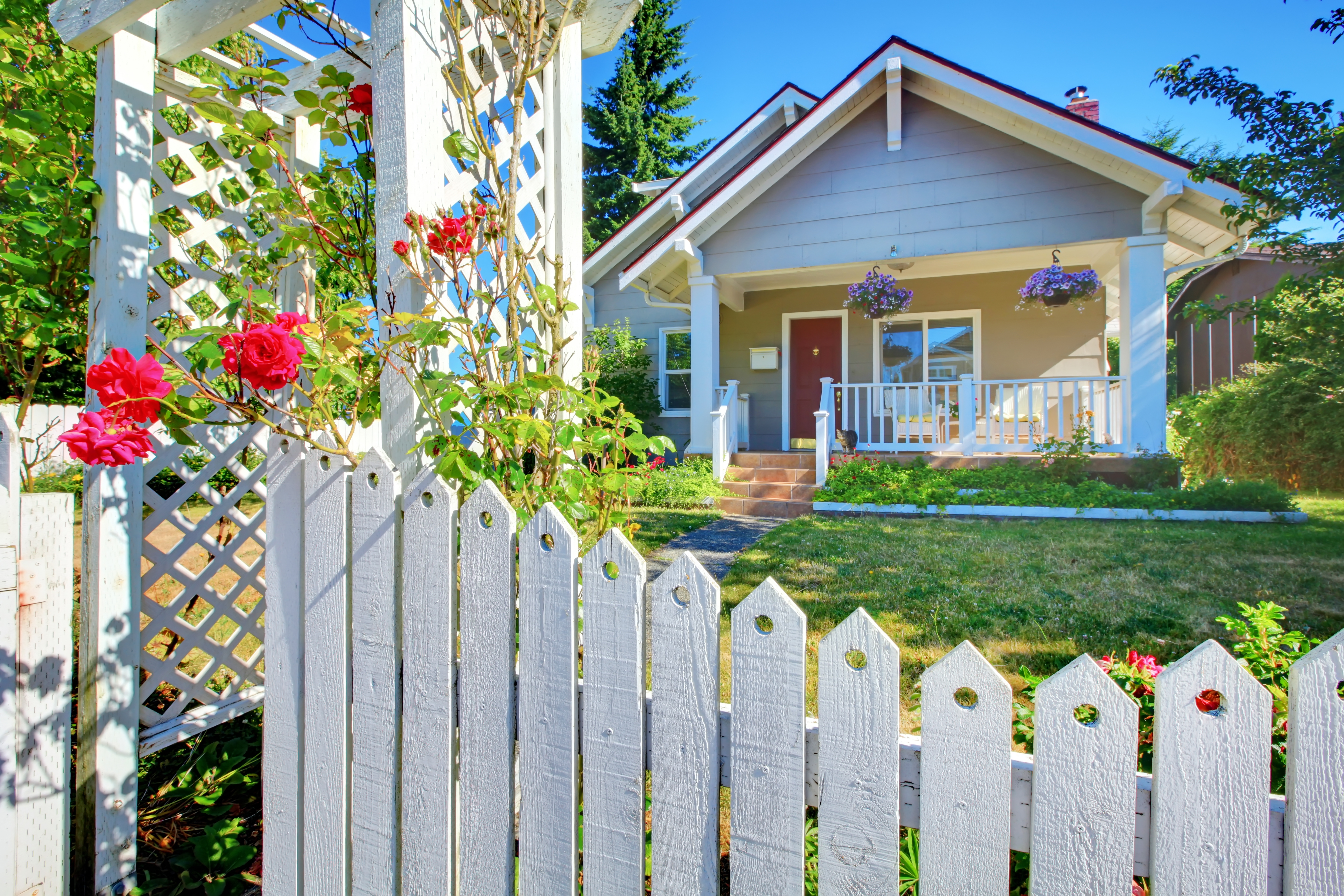 House tucked behind a beautiful white picket fence and green grass and flowers.
