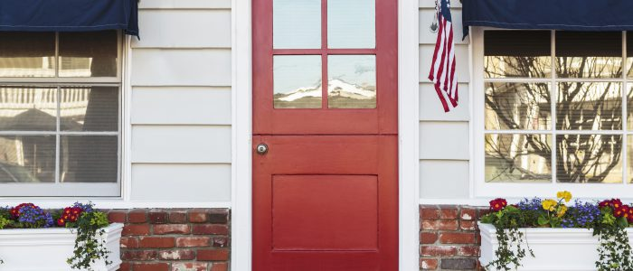 Photo of front of a home with a red door as the center focal point.