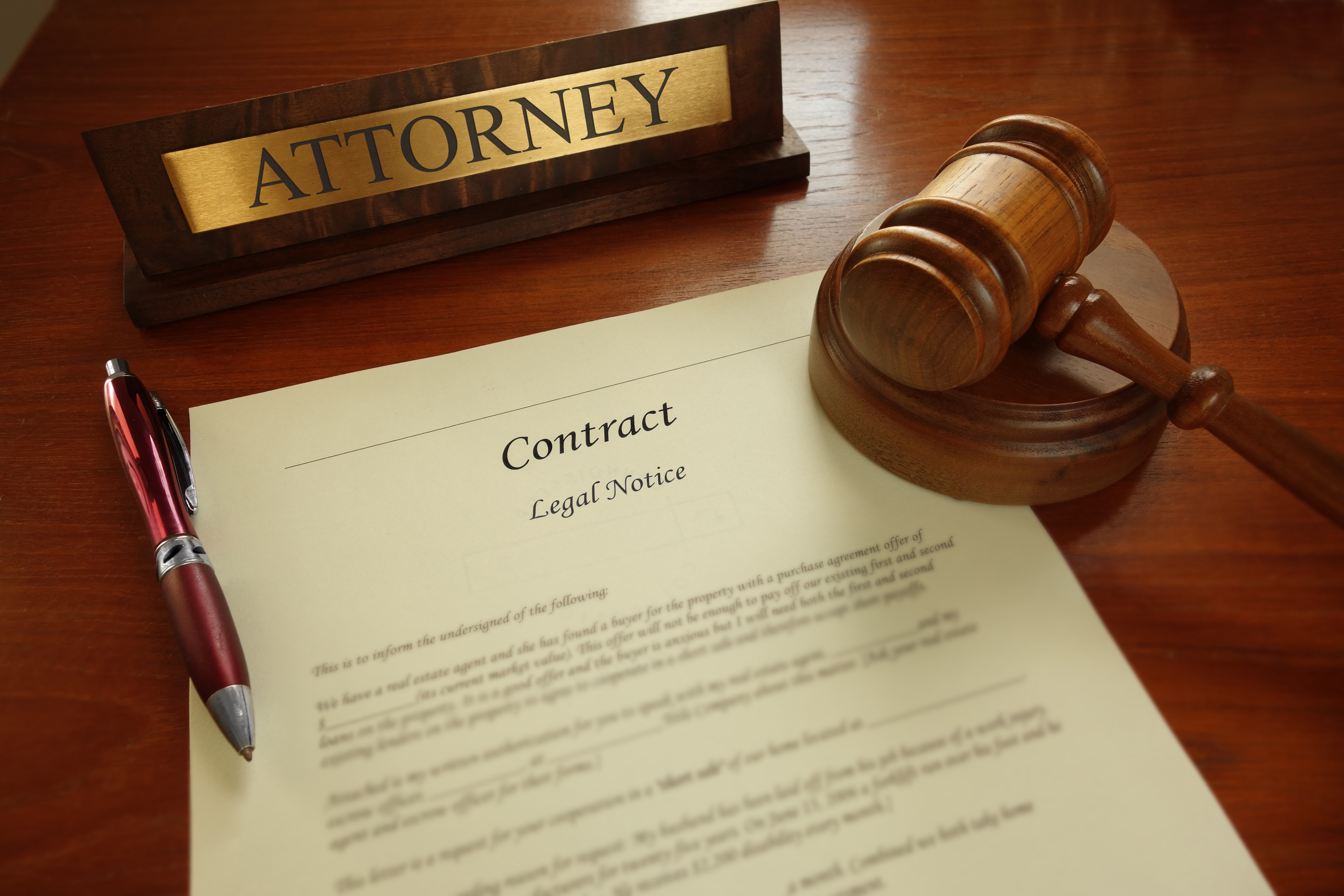 Legal contract with gavel and Attorney name plate on a desk