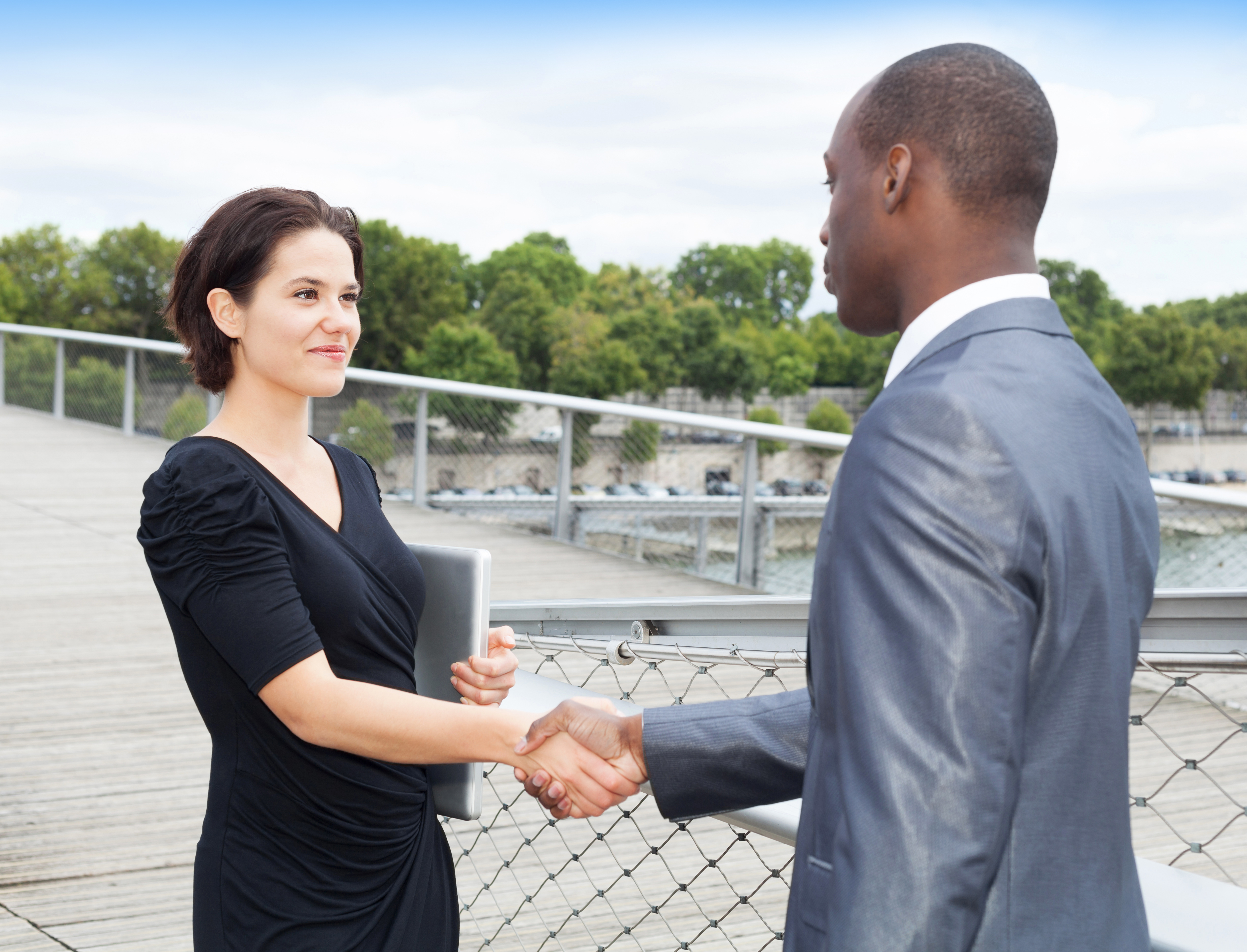 REALTOR and client shaking hands outside