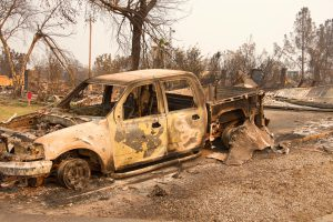 Charred truck in front of home burned to the ground in the recent wild fire fire storm in Redding, California. Smoke and ash in the air as the fire continues to burn several miles away.