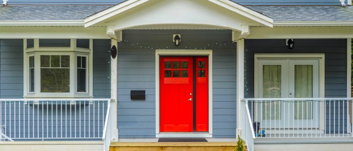 Close up photo of blue-gray home with red door and stairs leading to the entrance