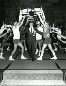Bill Moore on stage walking underneath lifted chairs and smiling