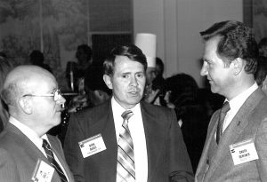 Jim Gale speaking with group of men at a conference