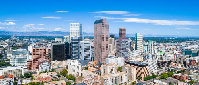 Aerial Drone view high above Denver , Colorado Downtown Skyline Cityscape August 2018 August Summer in the Mile High City Skyscrapers rise up in front of the Rocky Mountains and Colorado State Capitol building