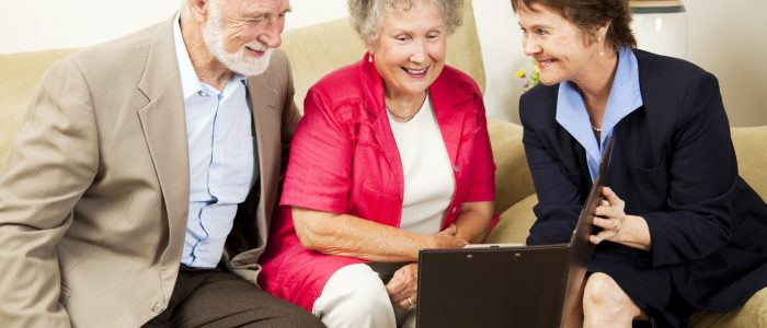 Saleswoman meets with senior couple in their home. Could be real estate life insurance etc.