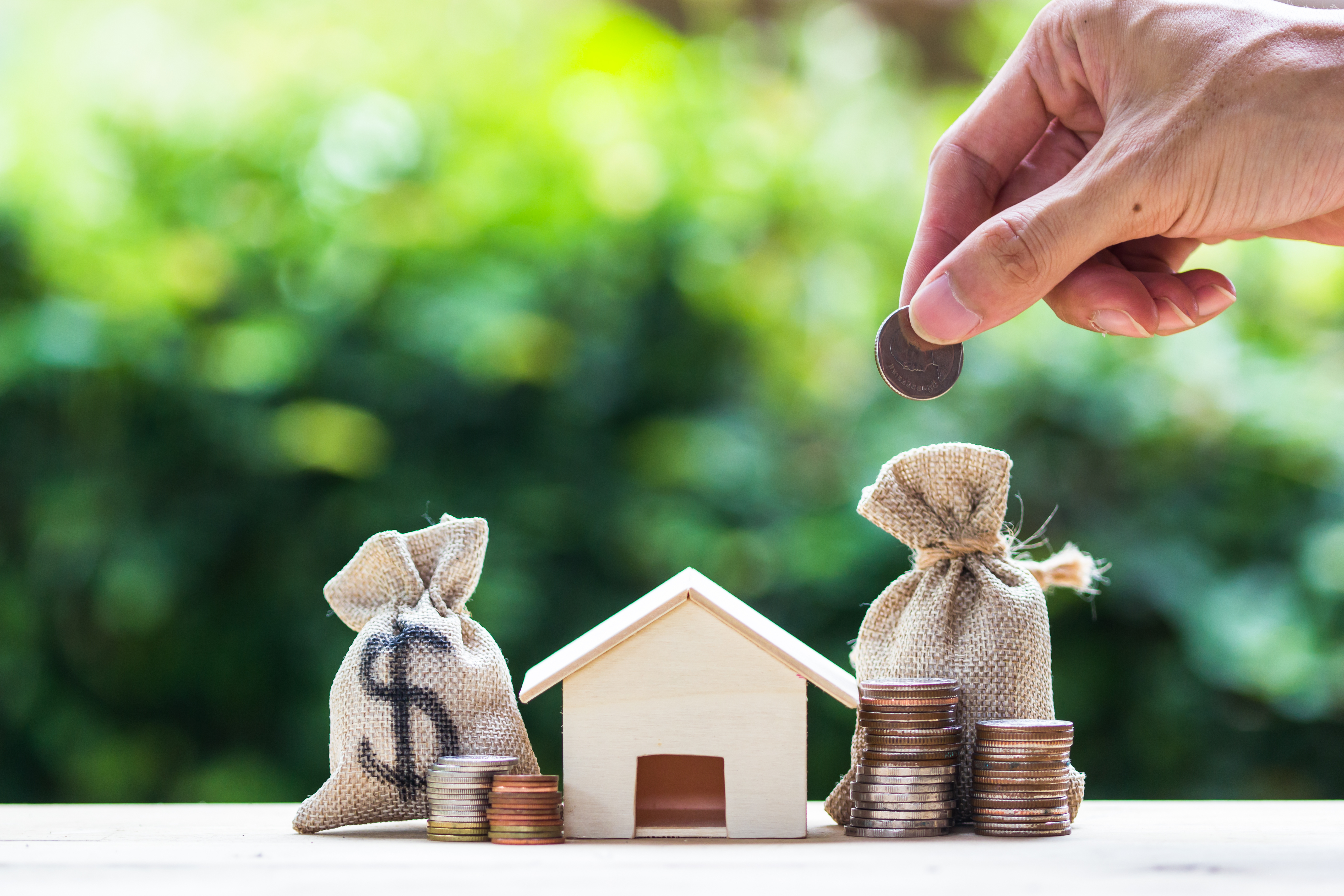 Saving money, home loan, mortgage, a property investment for future concept : A man hand putting money coin over small residence house and money bag